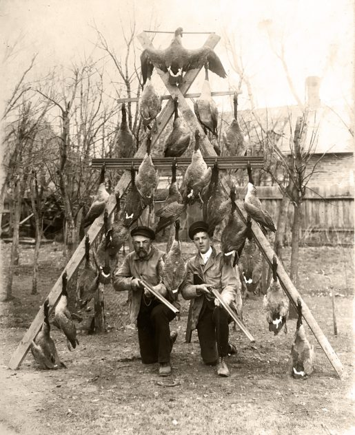 archival photo of two hunters and an a-frame of Canada Geese